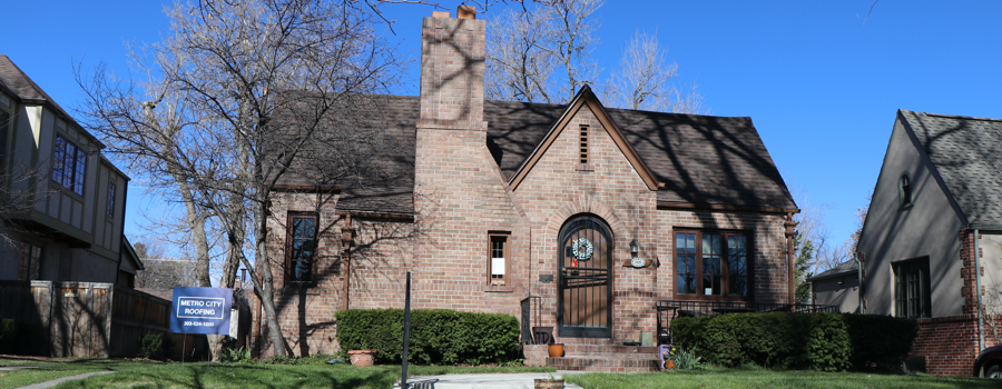 tan brick home with new dark brown asphalt shingle roof with blue sky in Denver, Colorado